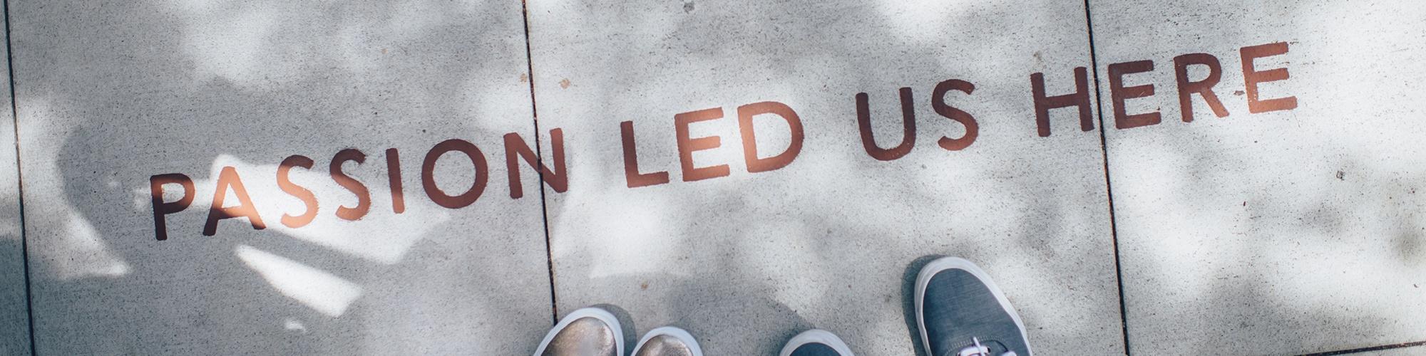 """Symbolbild: Gehweg mit der Aufschrift """"passion led us here"""""""
