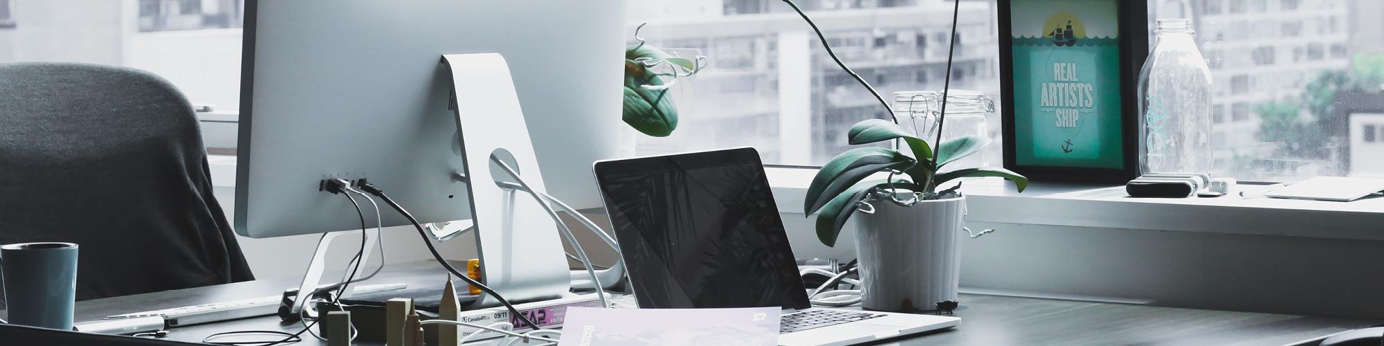 Symbolbild Schreibtisch: Zwei Arbeitsplätze mit Laptop und Computer