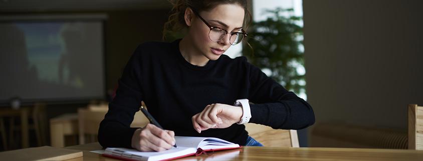 Symbolbild Zeitmanagment: Frau mit Brille sitzt an einem Tisch, schreibt etwas und schaut auf Armbanduhr