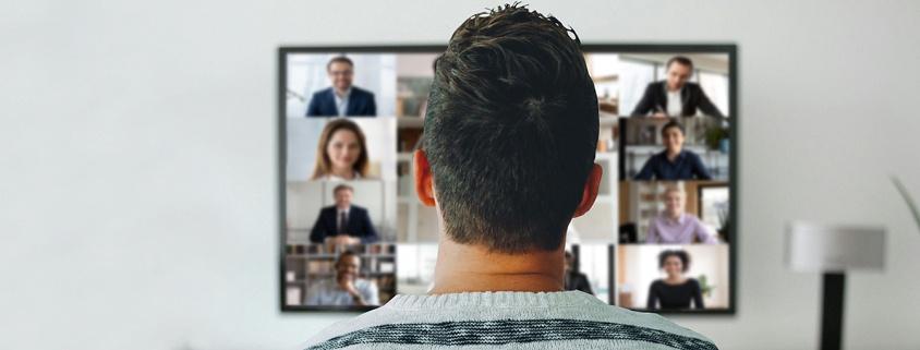 Symbolbild Video: Mann sitzt vor Fernseher und hat eine Videokonferenz