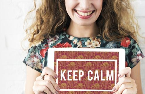 """Symbolbild Ideenreich: lächelnde Frau hält Schild mit der Beschriftung """"keep calm"""" in der Hand"""