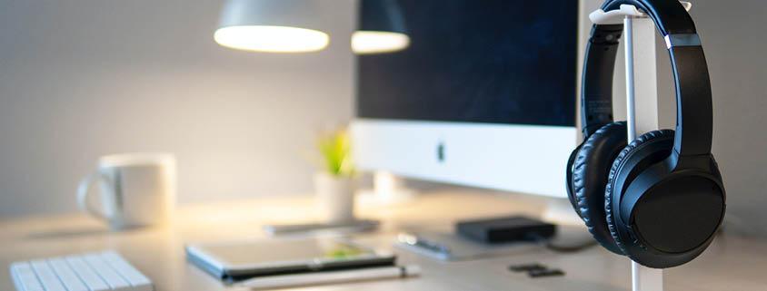 Symbolbild Technik: Kopfhörer auf einem Ständer und im Hintergrund ein Schreibtisch mit Computer