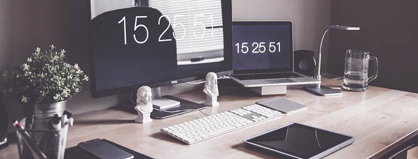 Symbolbild Schreibtisch: Ein MacBook und ein PC Bildschirm auf einem Schreibtisch