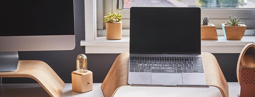 Symbolbild Arbeitsplatz: Ein Schreibtisch auf dem ein Laptop und ein angeschnittener Computer steht